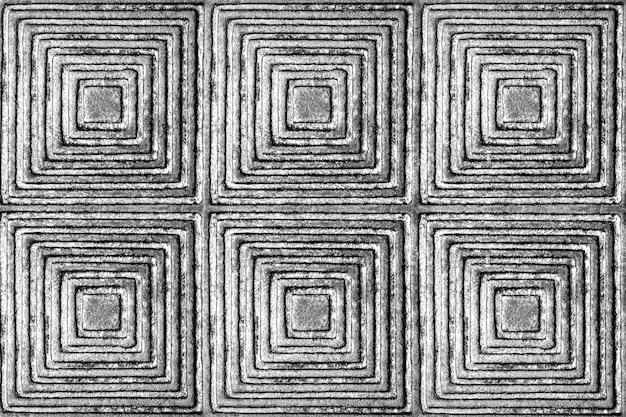 La texture d'une surface métallique avec un motif en forme de carrés et de losanges en noir et blanc.