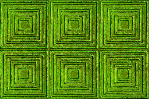 La texture de la surface métallique avec un motif en forme de carrés et de losanges en vert.