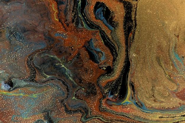 Texture de taches mélangées à l'encre liquide bleu et or.