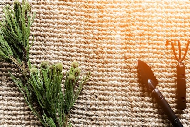 Texture de tapis de rotin avec outil de jardin et branche d'arbre
