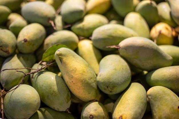 Texture de tas de mangues vertes fraîches à vendre sur le marché.