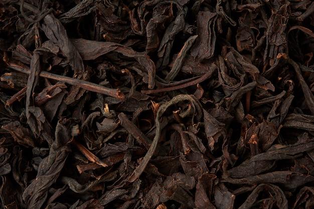 Texture de thé à feuilles longues noir sec, vue de dessus, ingrédients pour une boisson chaude