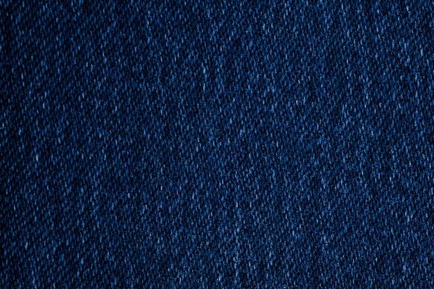 Texture de tissu jeans bleu foncé, surface bouchent fond