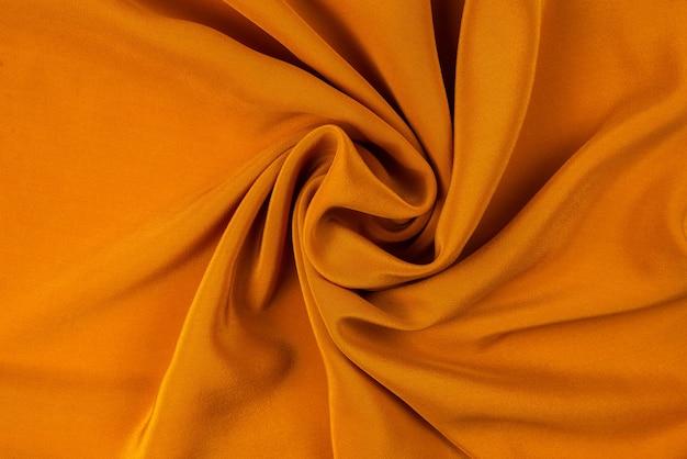 La texture de tissu de luxe en soie dorée ou en satin peut être utilisée comme fond abstrait. vue de dessus.