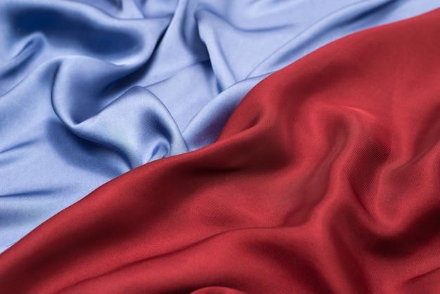 Texture de tissu de luxe en soie rouge et bleue ou satin.