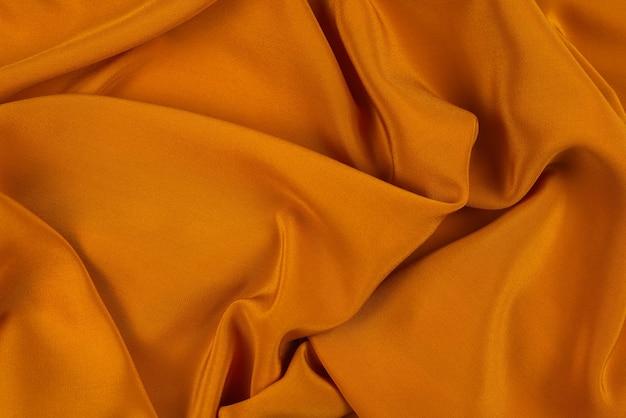 La texture de tissu de luxe en soie ou satin doré peut être utilisée comme fond abstrait. vue de dessus.