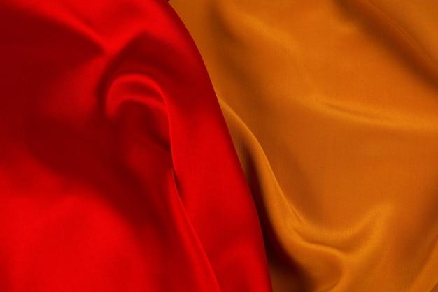 La texture de tissu de luxe en soie ou satin rouge et orange peut être utilisée comme fond abstrait. vue de dessus.
