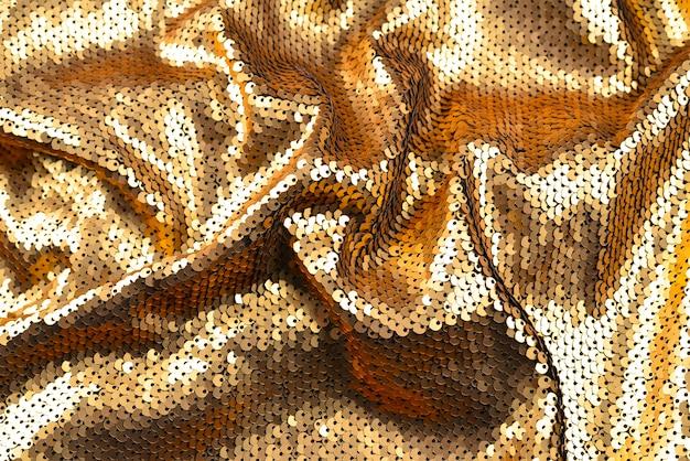 Texture de tissu paillettes dorées.