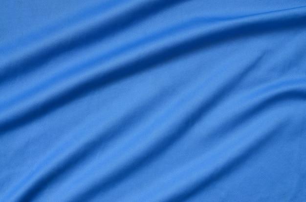 Texture de tissu en polyester bleu détaillé avec de nombreux plis