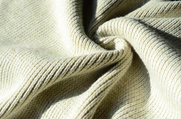 Texture de tissu d'un pull tricoté jaune doux. macro image de la structure des reliures en fils