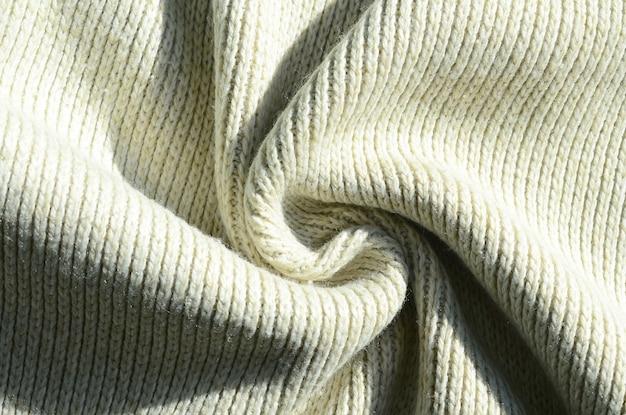 Texture de tissu d'un pull tricoté jaune doux