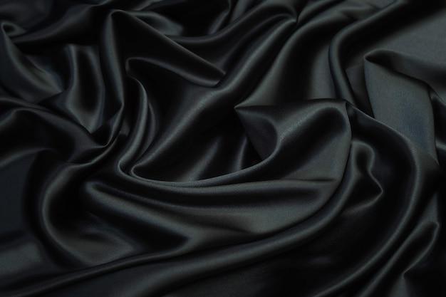 Texture de tissu de satin de soie noire élégante lisse comme fond abstrait. motif luxueux pour la conception.