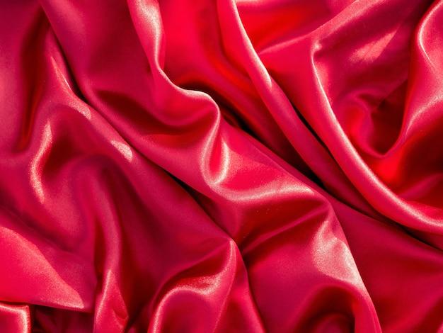 Texture de tissu en soie rouge ou satin. fond de vagues de tissu rouge, vue de dessus.