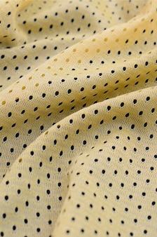 Texture de tissu de vêtements de sport jersey jaune et fond avec beaucoup de plis