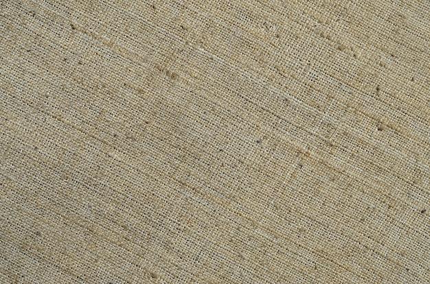 Texture d'une toile grise en jute ancienne et grossière.