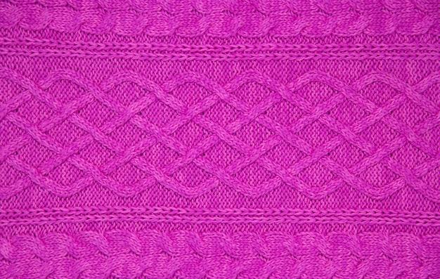 Texture tricotée en fil de laine rose. modèle de câble tressé à 12 points tricoté à la main. horizontal. fermer