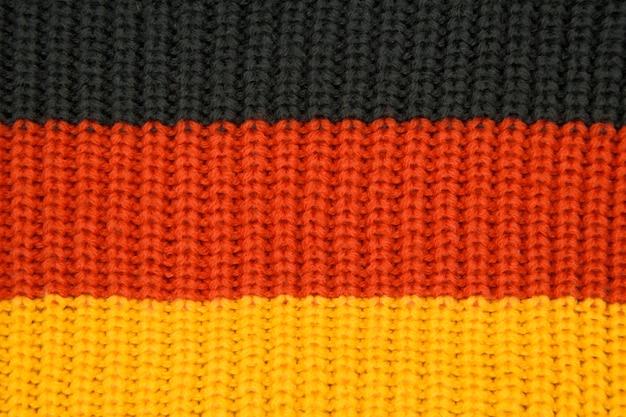 Texture tricotée gros plan, couleurs du drapeau de l'allemagne noir
