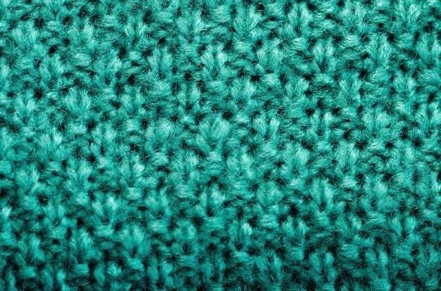 Texture tricotée. tissu à motifs en laine. fond turquoise, espace copie