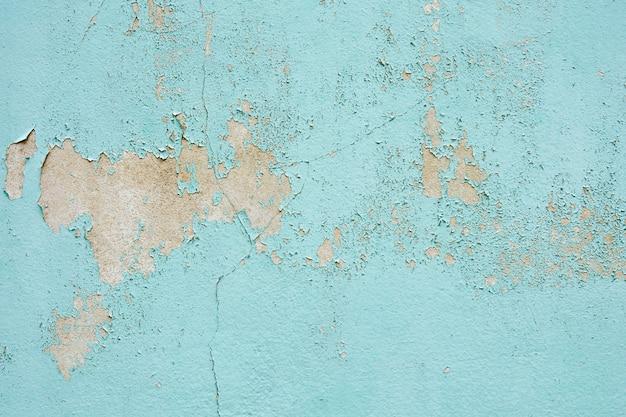 La texture de la vieille peinture bleue est ébréchée et fissurée au mur