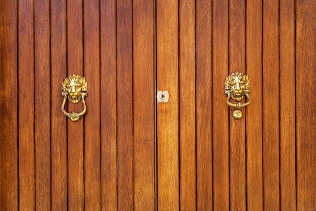 Texture d'une vieille porte en bois en bois avec poignées en métal en forme de tête de lion sur l'île