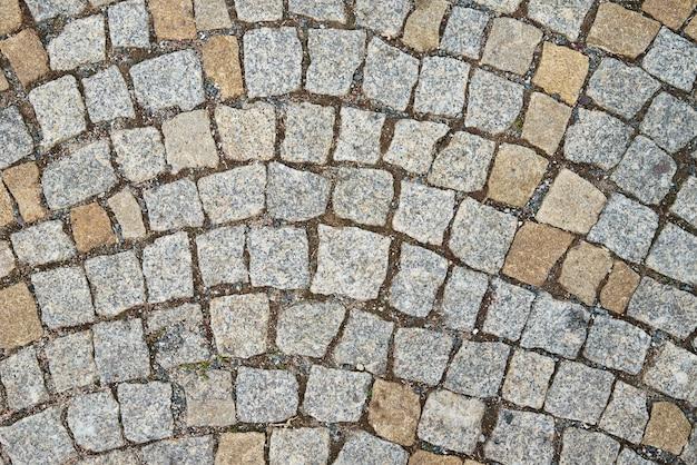 Texture avec le vieux fond abstrait en pierre de chaussée avec des briques