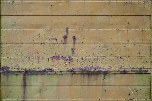 Texture d'un vieux mur en métal orange avec des dommages importants