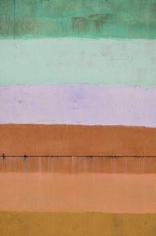 Texture d'un vieux mur en métal, peint en plusieurs couleurs