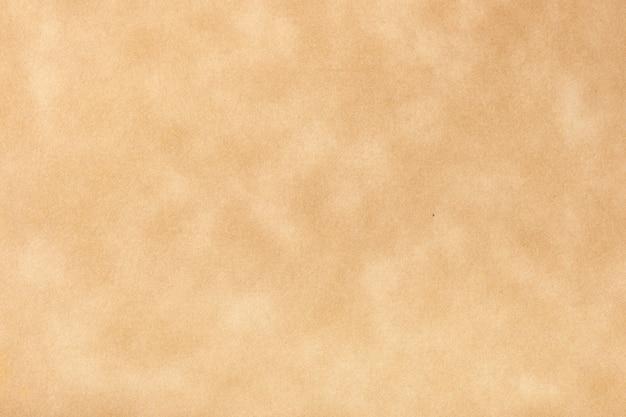 Texture de vieux papier beige, fond froissé. toile de fond de surface grunge marron vintage. structure de carton parchemin artisanal.