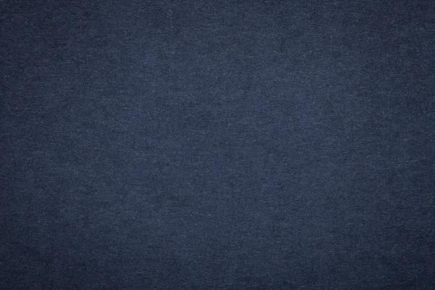 Texture de vieux papier bleu marine, agrandi. structure en carton denim foncé et dense