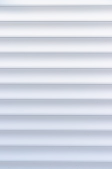 Texture de volet roulant. fond avec des rayures métalliques en blanc. volets roulants en fer de couleur blanche.