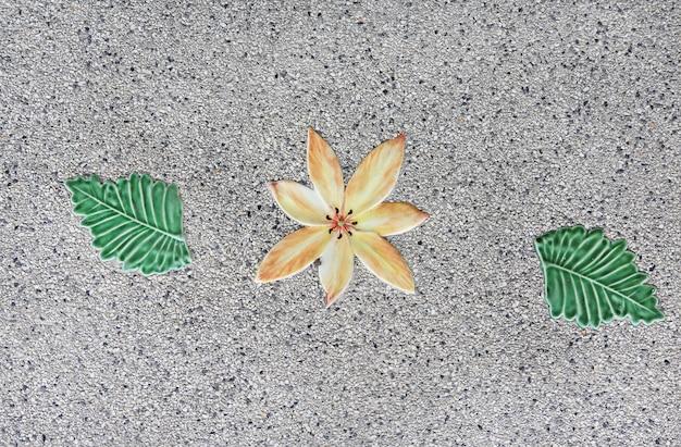 Les textures de fleur en céramique et de feuille sur le sol.