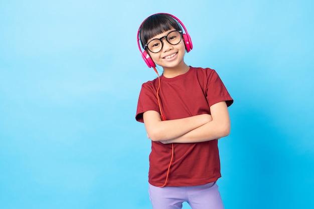 Thai asia girl kid écoute de la musique, portant des écouteurs roses