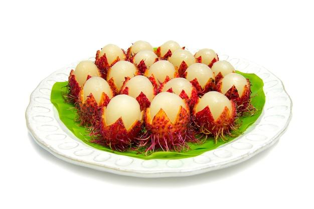 Thai fruits ramboutan doux pour l'été mis sur la vue de côté de feuille de bananier isolé