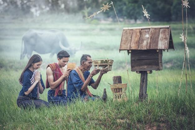 Thaïlandais faisant des offrandes sur un champ