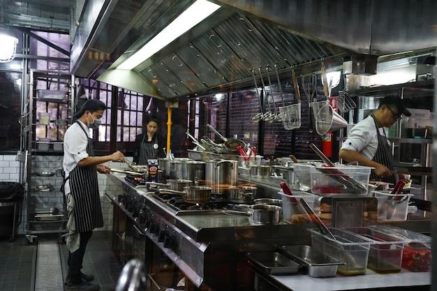 Thaïlande - 10 octobre 1818: 2 chefs cuisiniers cuisiniers préparent la nourriture dans un restaurant à cuisine ouverte.