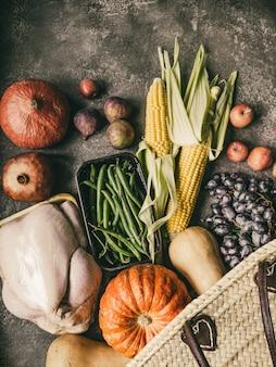 Thanksgiving shopping avec de la volaille crue, des légumes et des fruits.
