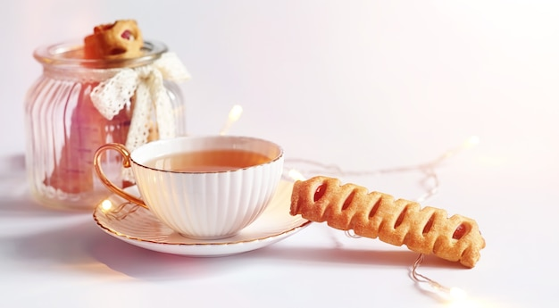 Thé accompagné de viennoiseries au petit déjeuner. bonbons et pâtisseries aux noix pour le thé sur fond blanc. une tasse de café et des galettes.