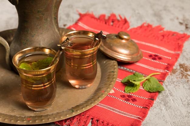 Thé arabe dans des verres à la menthe sur plateau