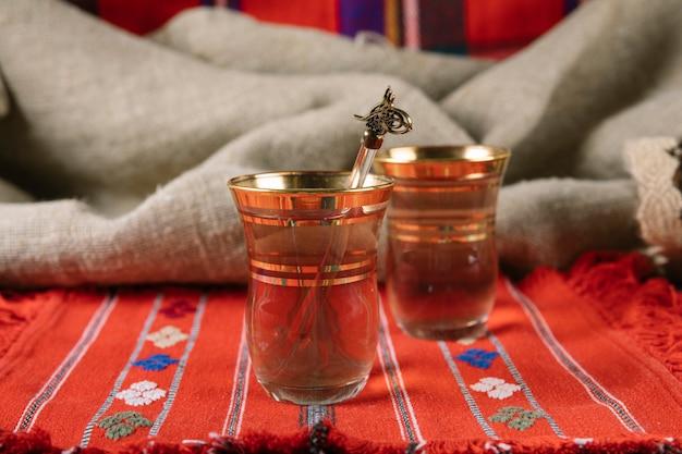 Thé arabe dans des verres sur la table rouge