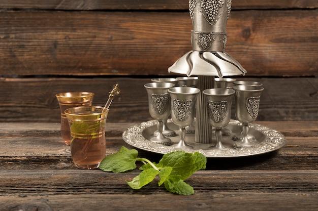 Thé arabe dans des verres avec des tasses sur le plateau