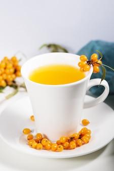 Thé à l'argousier dans une tasse blanche avec des baies avec une branche sur une serviette en papier naturel.