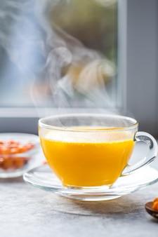 Thé à l'argousier dans une tasse en verre avant la fenêtre. boisson aux vitamines aux herbes