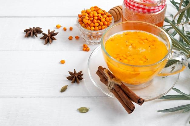 Thé d'argousier dans une tasse en verre baies crues fraîches et feuilles de miel, d'anis et de cannelle