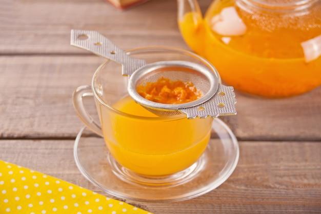 Thé à l'argousier dans une tasse en verre. thé de vitamines à base de plantes.
