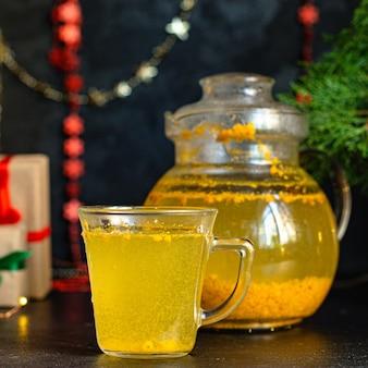 Thé à l'argousier dans une théière et dans une tasse transparente sur la table christmas tea party nouvel an boisson d'hospitalité