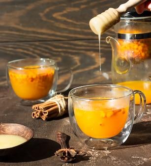 Thé d'argousier épicé chaud coloré avec de la cannelle, de l'anis et du miel dans une tasse en verre