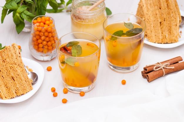 Thé à l'argousier, menthe, miel, cannelle, gâteau au miel en couches medovik.