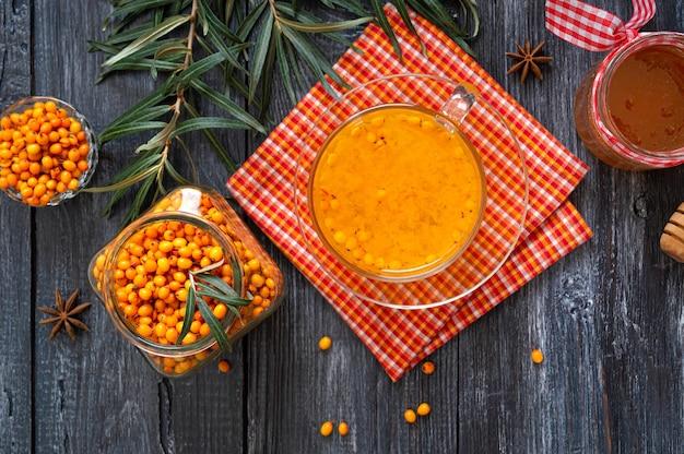 Thé d'argousier naturel chaud et coloré dans une tasse en verre de baies crues fraîches et de feuilles d'anis au miel