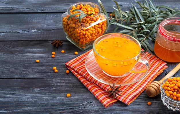 Thé d'argousier naturel chaud et coloré dans une tasse en verre de baies crues fraîches et de miel