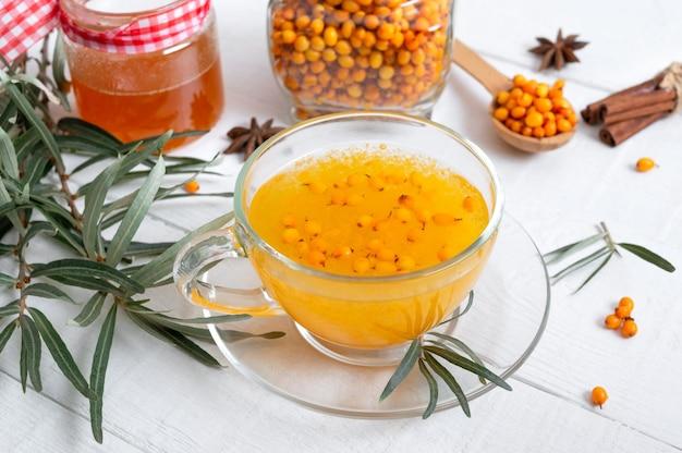 Thé d'argousier naturel chaud et coloré dans une tasse en verre concept de boissons chaudes de saison